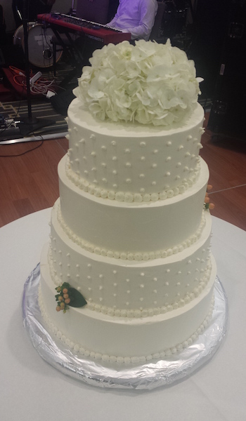 four tiered white cake with flowers